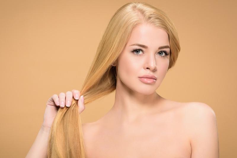 Model Holding Long Blonde Hair