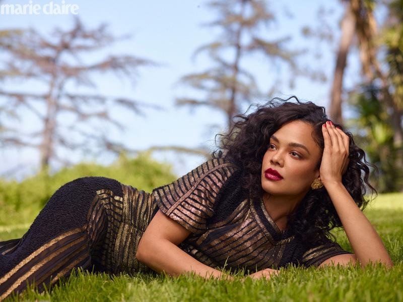 Laying in grass, Tessa Thompson wears Chanel dress with Mallarino earrings