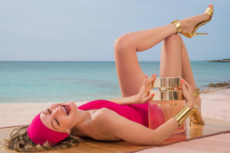 All smiles, Gigi Hadid poses with Michael Kors' Wonderlust scent