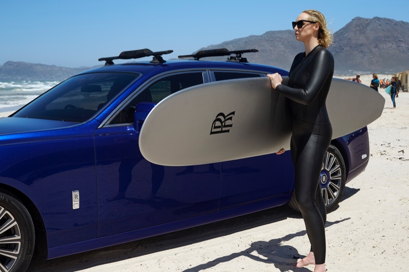 Heading to the beach, Gwendoline Christie poses with a surfboard on set of Rolls-Royce Phantom film