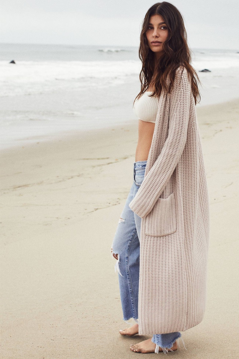 Posing at the beach, Camila Morrone wears Naked Cashmere collaboration