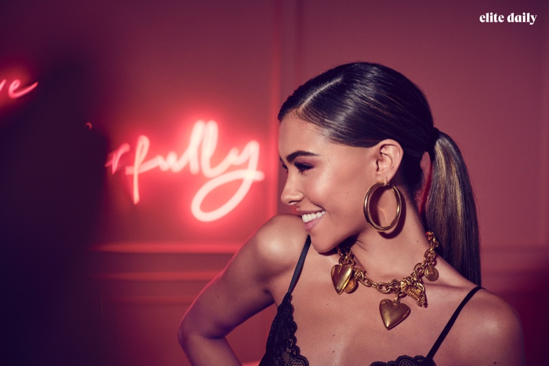 All smiles, Madison Beer wears Intimisismi top, Jennifer Fisher earrings and Versace necklace
