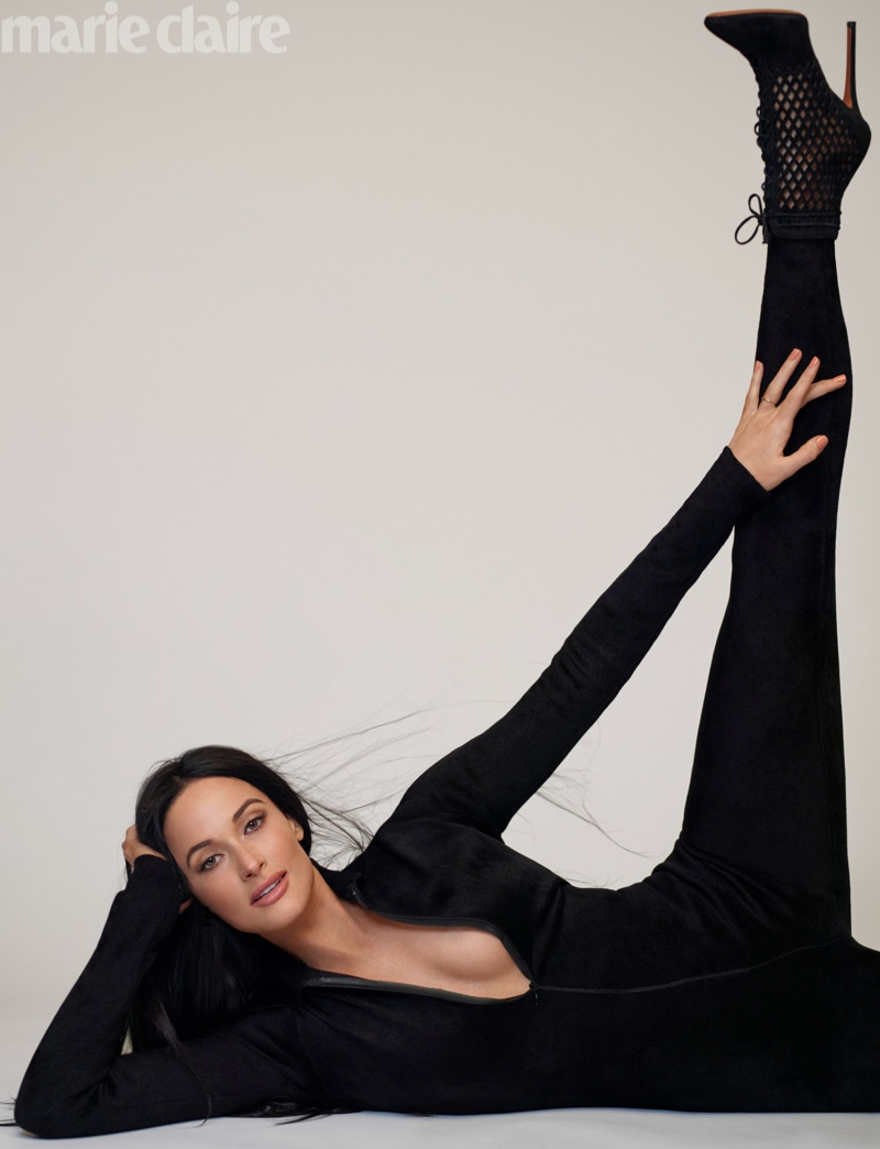 Kicking up her leg, Kacey Musgraves poses in Mason Alaïa jumpsuit and boots