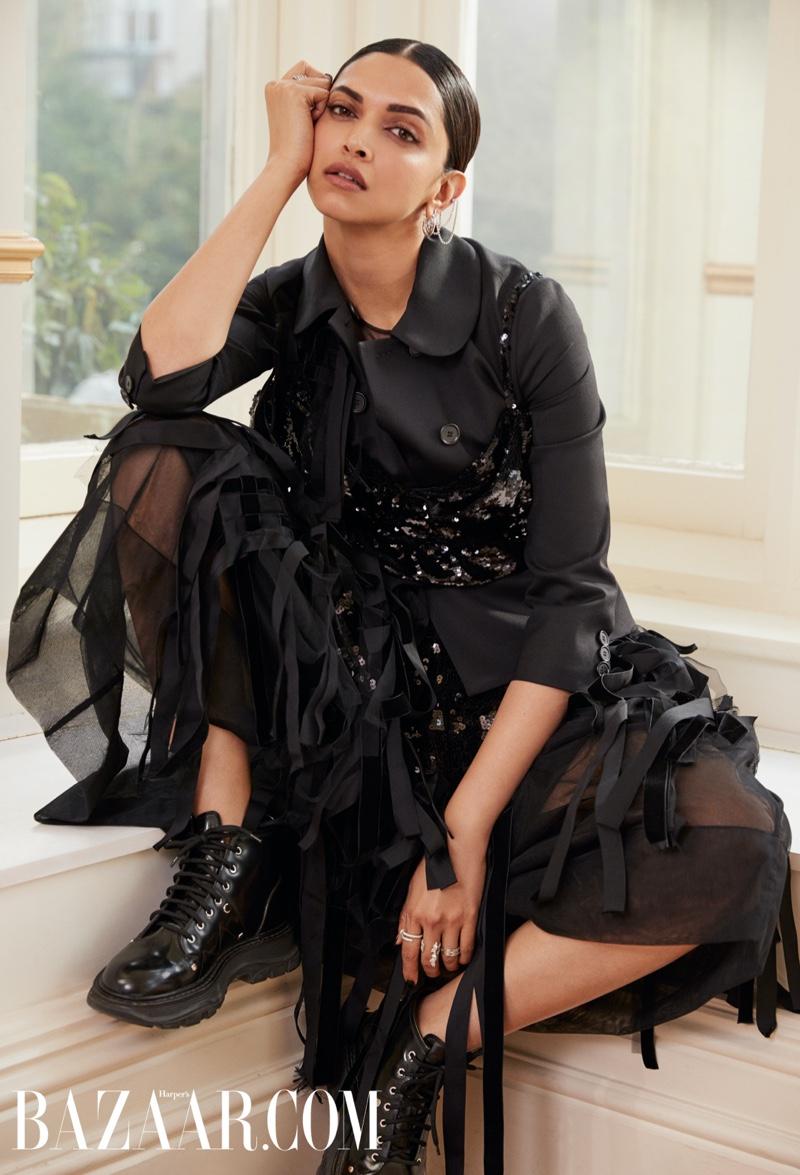 Dressed in black, Deepika Padukone wears Simone Rocha jacket, dress and top with Alexander McQueen boots