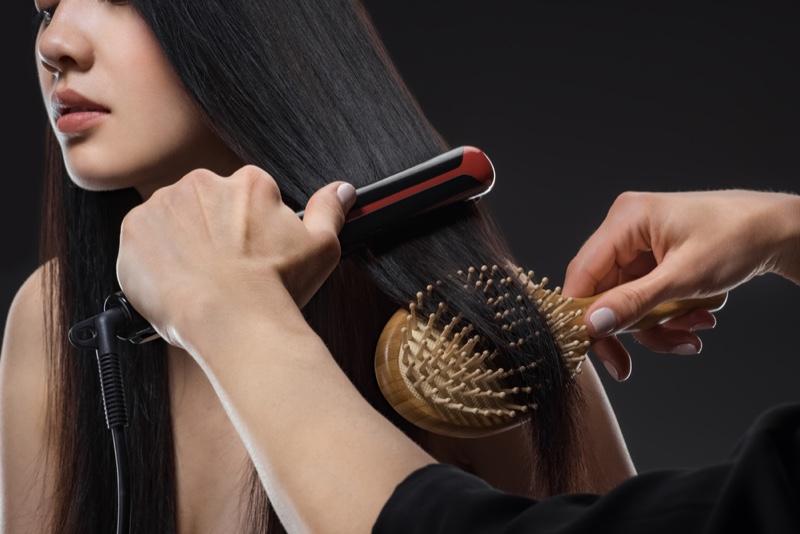 Hairstylist Straightening Brushing Model's Hair