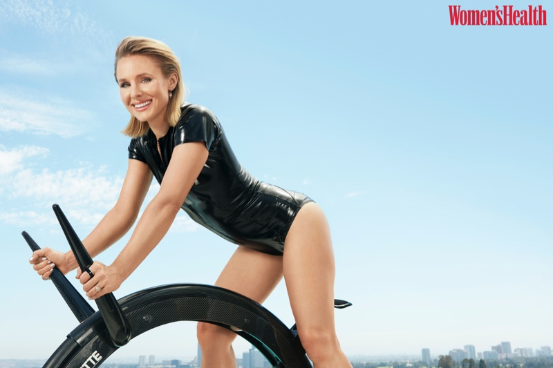 Kristen Bell rides a bike in Lisa Marie Fernandez one-piece