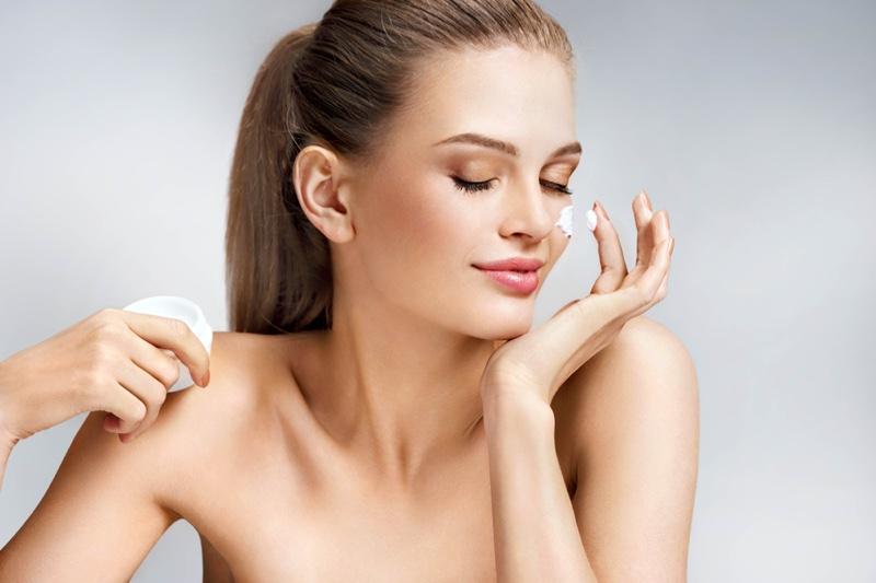 Model Applying Cream Smiling Beauty