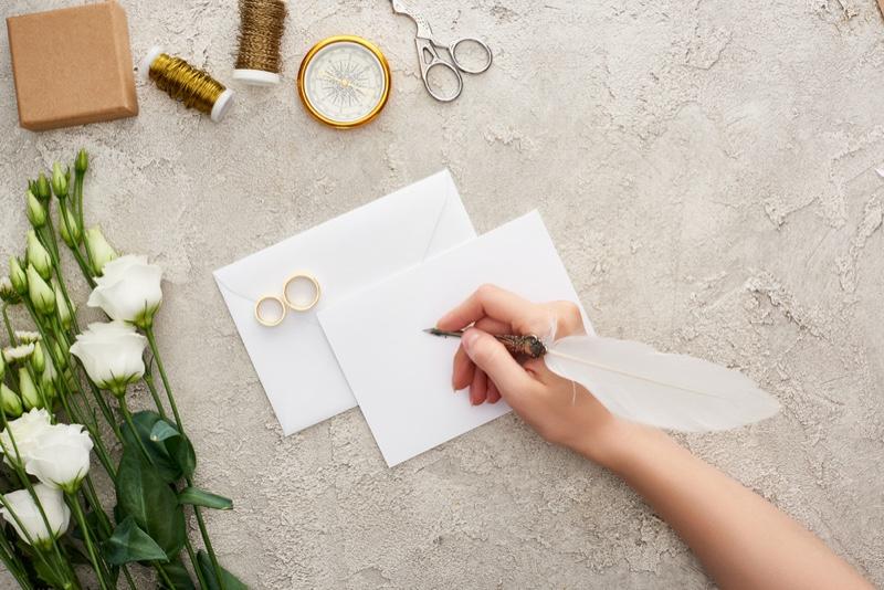 Woman's Hand Wedding Invitation Rings Thread Scissors Flowers