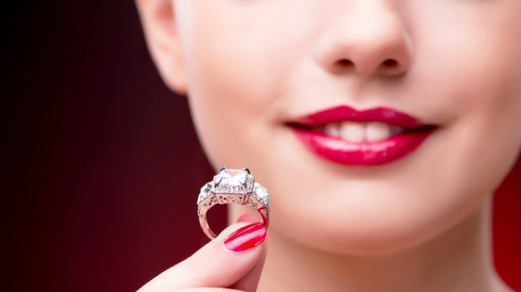 Closeup Model Holding Engagement Ring Red Nails