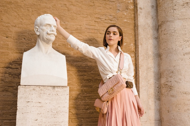 Kiernan Shipka poses with a statue for Fendi #BaguetteFriendsForever campaign