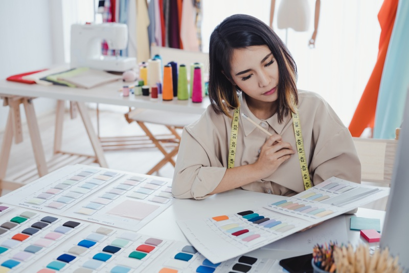 Asian Fashion Designer Looking at Fabric Swatches