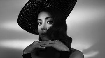 Captured in black and white, Aubrey Plaza wears Anna Kiki top with vintage Dior hat
