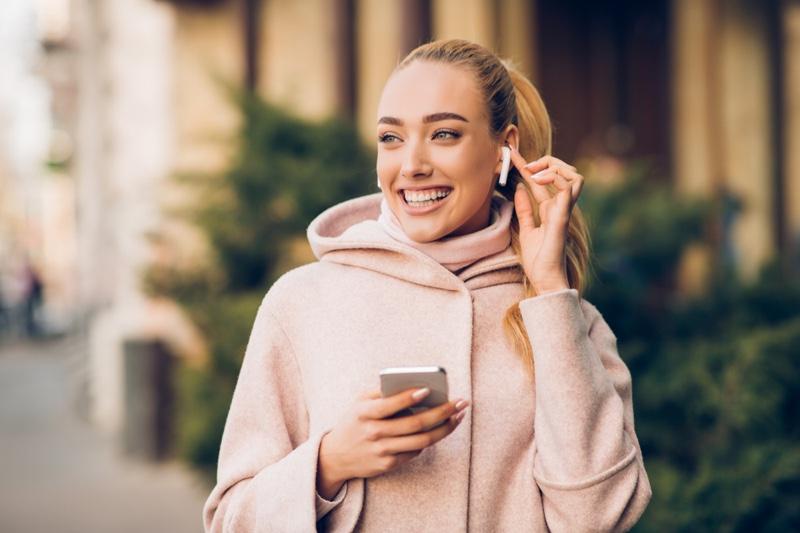 Blonde Woman Smiling Airpods Phone Pink Jacket