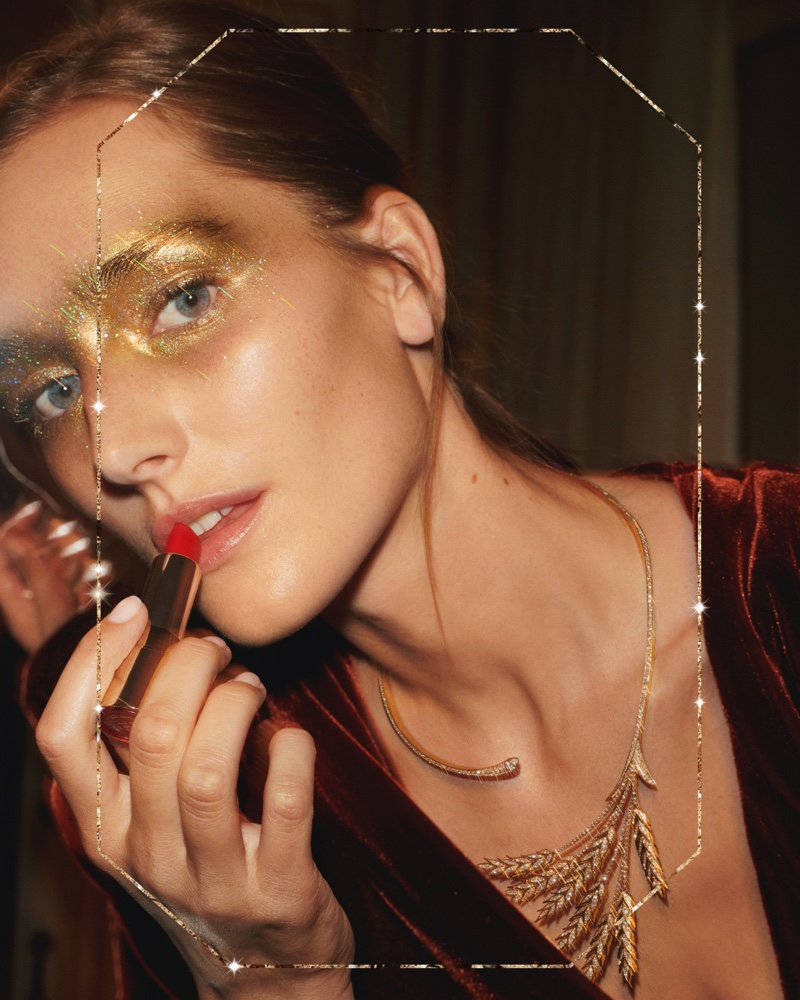Putting on lipstick, Josephine le Tutour appears in Boucheron Holiday 2019 campaign