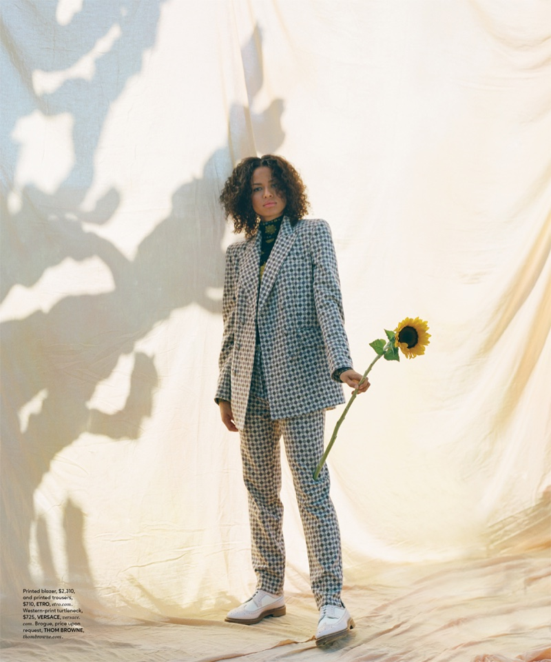 Suiting up, Gugu Mbatha-Raw poses in Etro blazer and trousers with Versace turtleneck and Thom Browne brogue