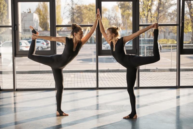 Two Women Wearing Black Acroyoga Poses