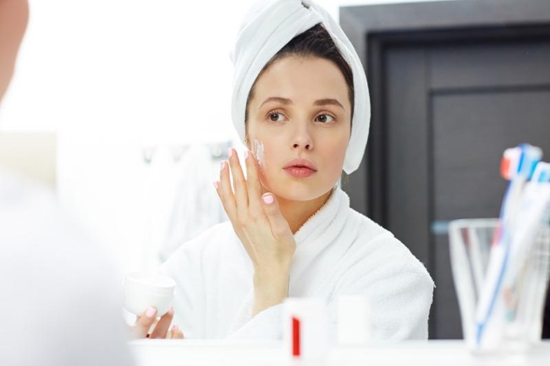 Woman Applying Moisturizer Towel Mirror