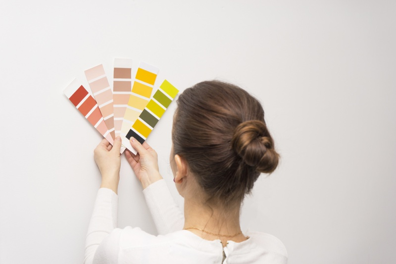 Woman Holding Paint Swatches Wall