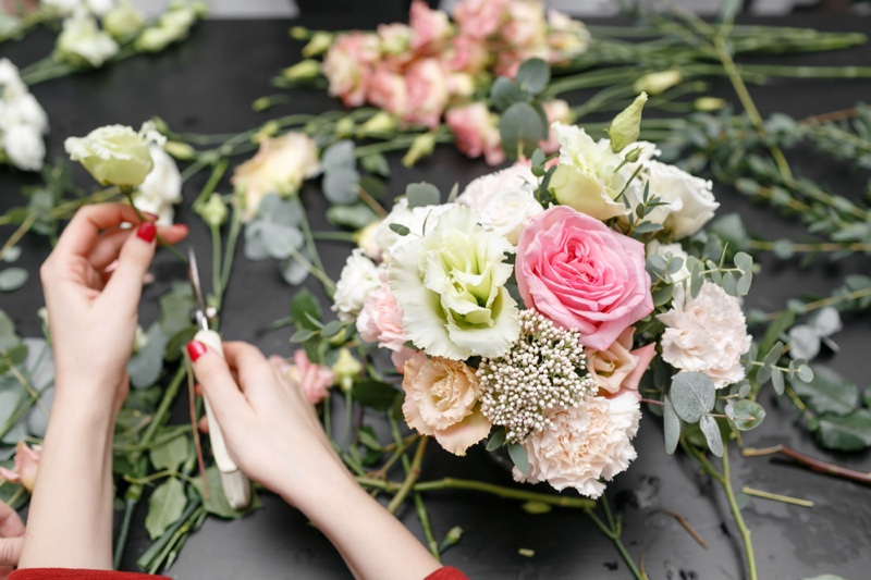 Woman's Hands Arranging Flowers Red Nails
