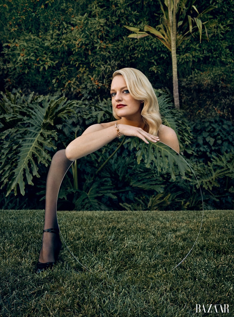 Actress Elisabeth Moss wears Tiffany & Co. jewelry, Falke tights and Gucci pumps