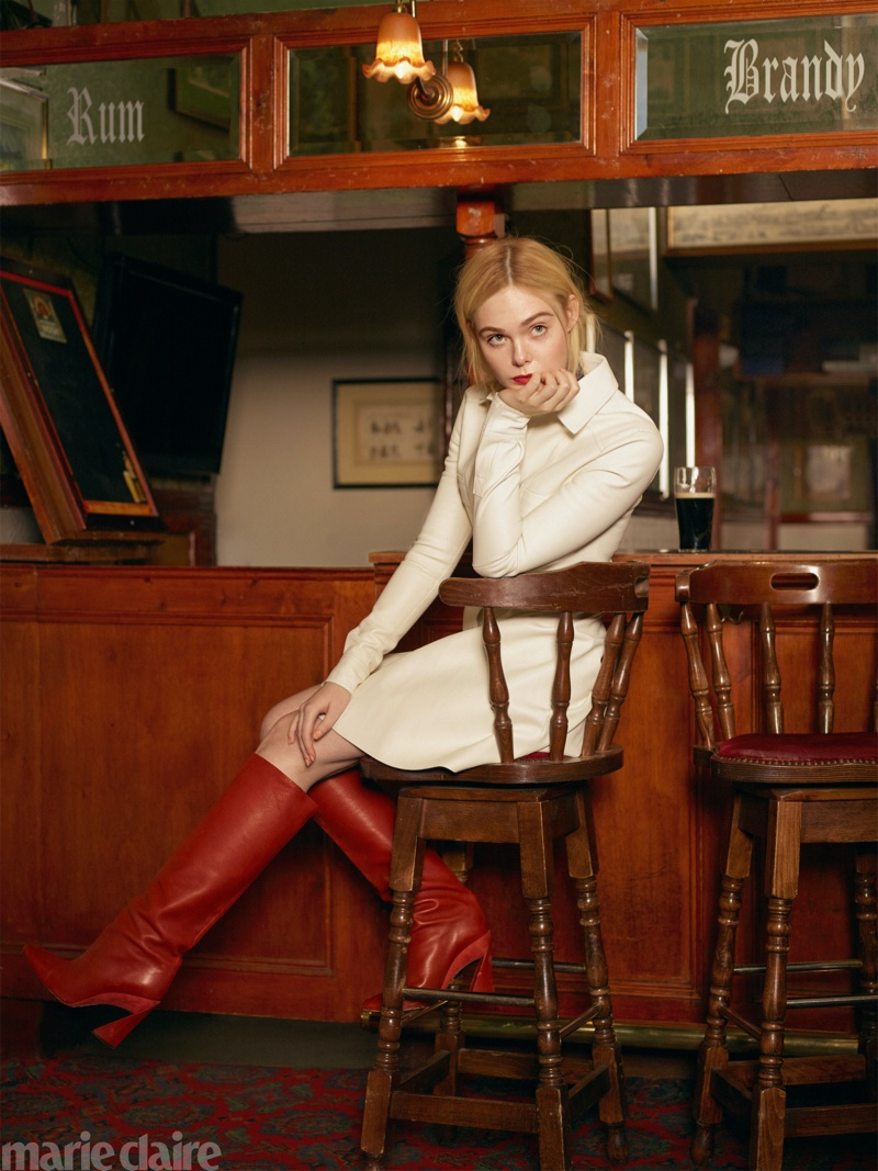 Posing at a bar, Elle Fanning wears Longchamp dress and Salvatore Ferragamo boots