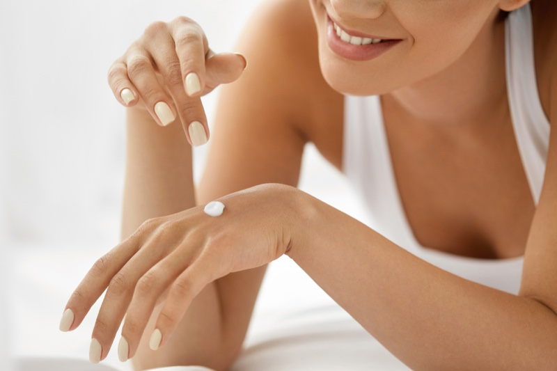 Woman Applying Cream Hand Manicured Nails