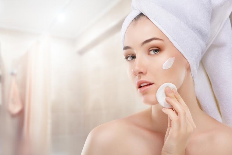 Woman Applying Face Cream Cotton Round Towel