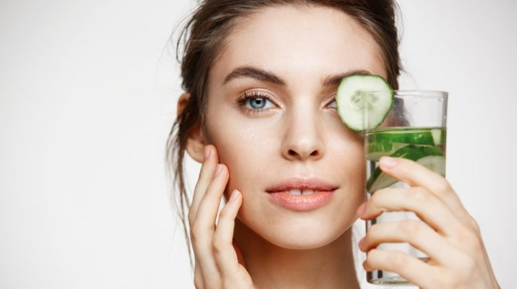 Beauty Model Holding Cucumber Water