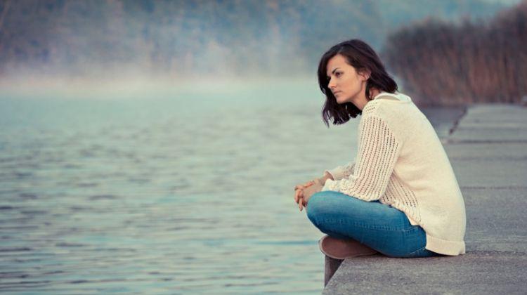 Brunette Woman Sitting Lake Water Sweater Jeans
