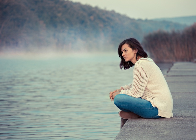 Brunette Woman Sitting Lake Water Sweater Jeans