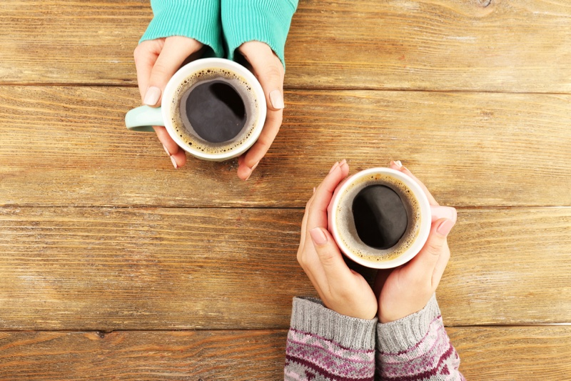 Female Hands Holding Coffee Cups