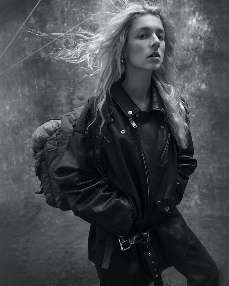 Hunter Schafer poses in Balenciaga jacket and pants with Galaxy Army Navy bag