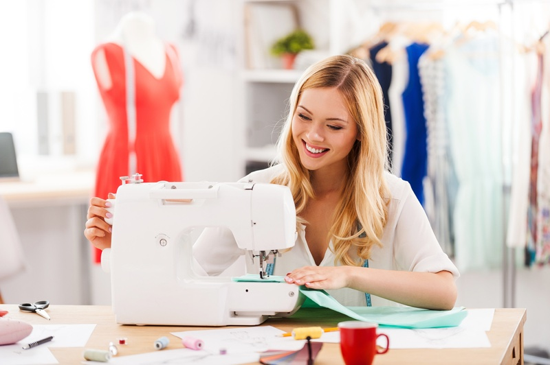 Smiling Blonde Woman Sewing Clothes