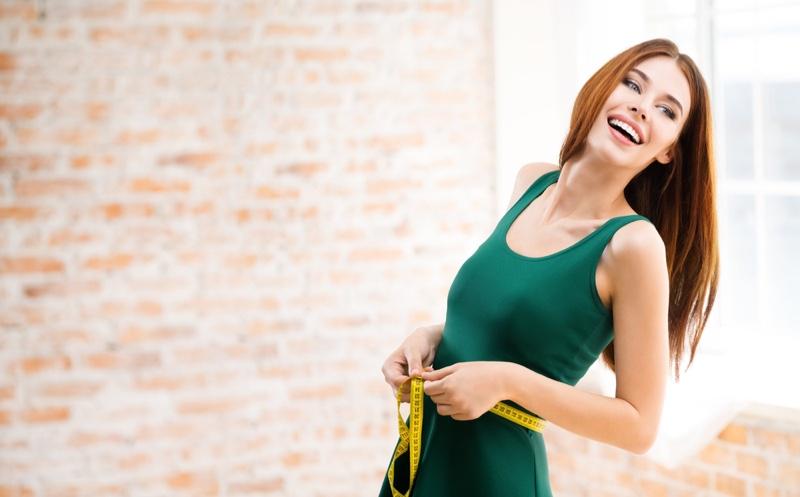 Smiling Woman Measuring Waist