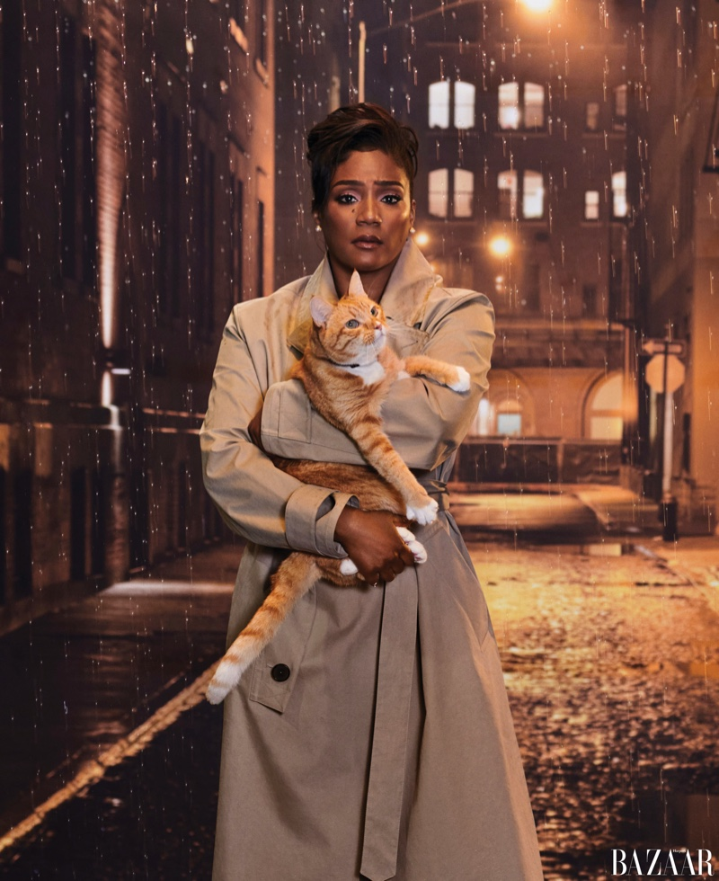 Posing with a cat, Tiffany Haddish wears Hermès trench coat with Tiffany & Co. earrings
