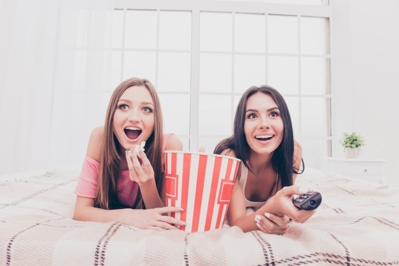 Two Girls Watching Movie Home Popcorn Bed