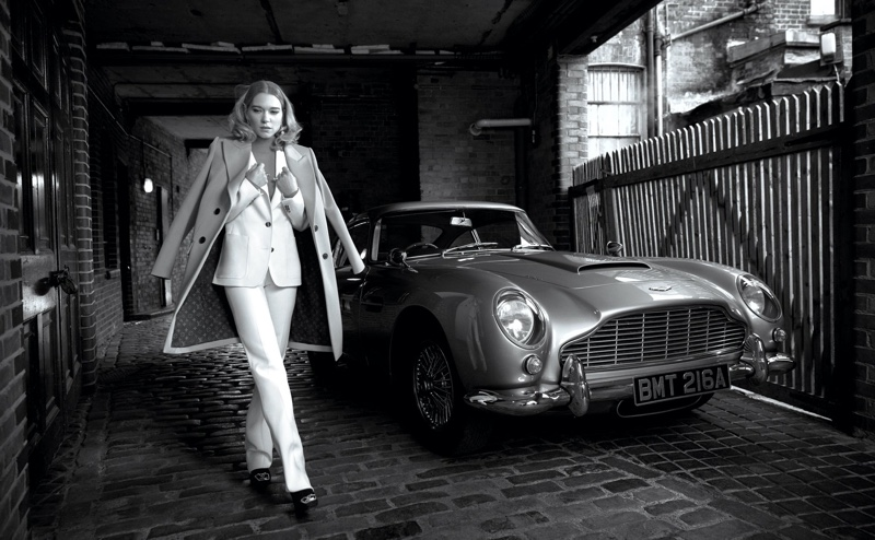 Suiting up, Lea Seydoux poses next to a vintage car in Louis Vuitton