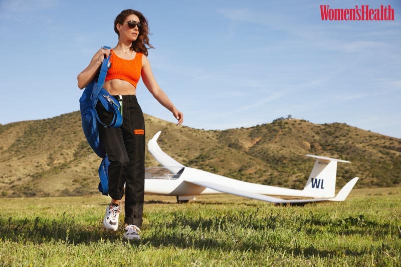 Alison Brie wears Versace top, Heron Preston pants, Alex Arigate sneakers and Carrera sunglasses