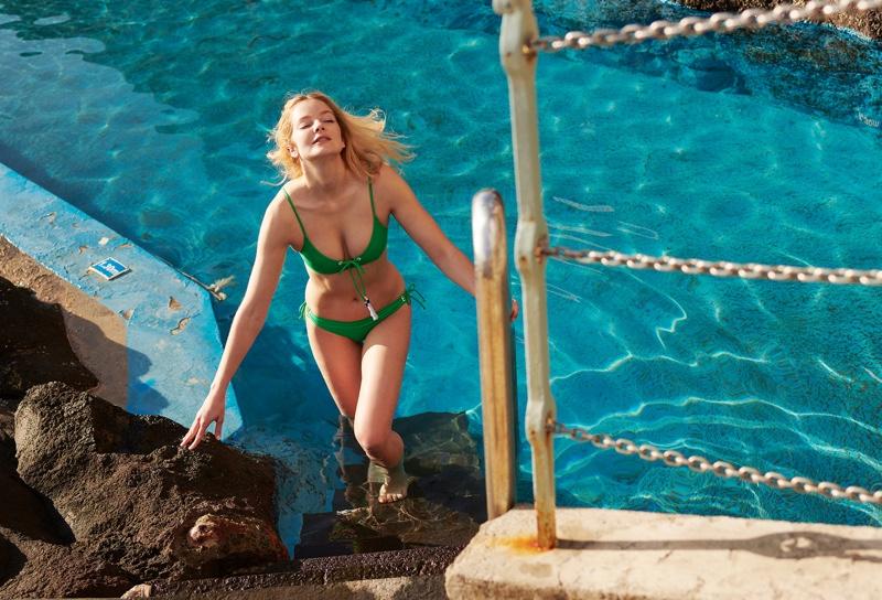 Soaking up the sun, Eniko Mihalik tries on green Emma Pake bikini set.