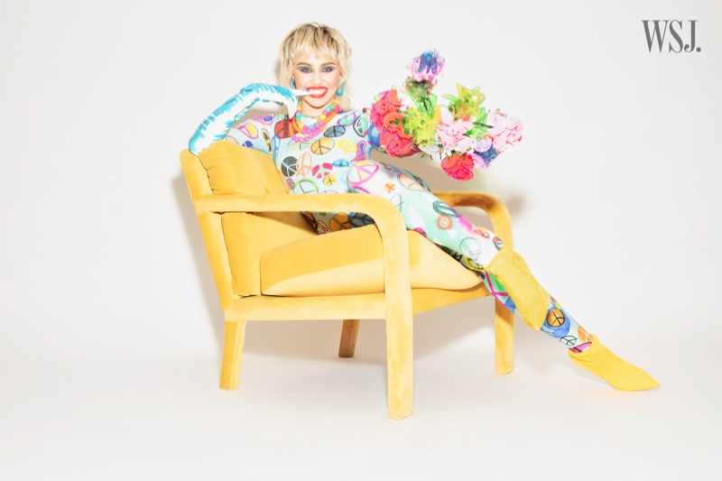 Sporting peace signs, Miley Cyrus poses with a flower bouquet.