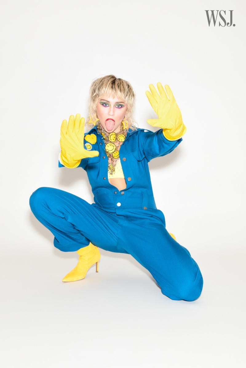 Miley Cyrus wears a blue jumpsuit with yellow accessories.