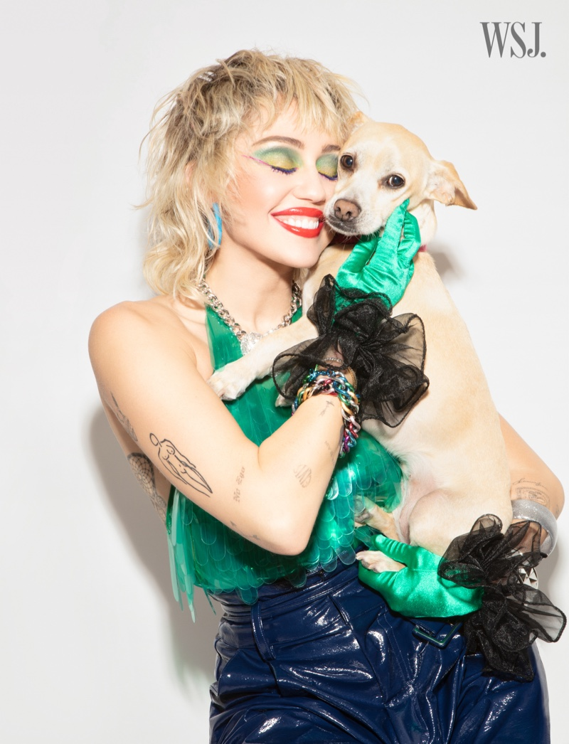 Posing with her dog, Miley Cyrus is all smiles.