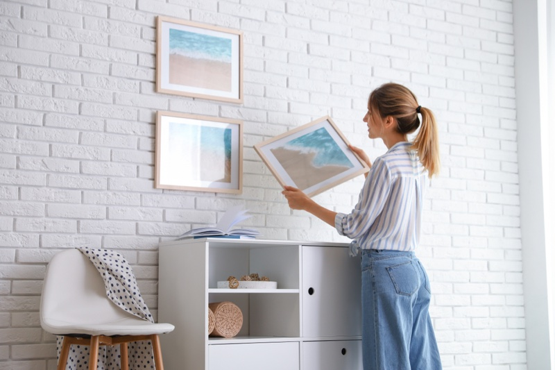Woman Decorating Home Hanging Picture Frames