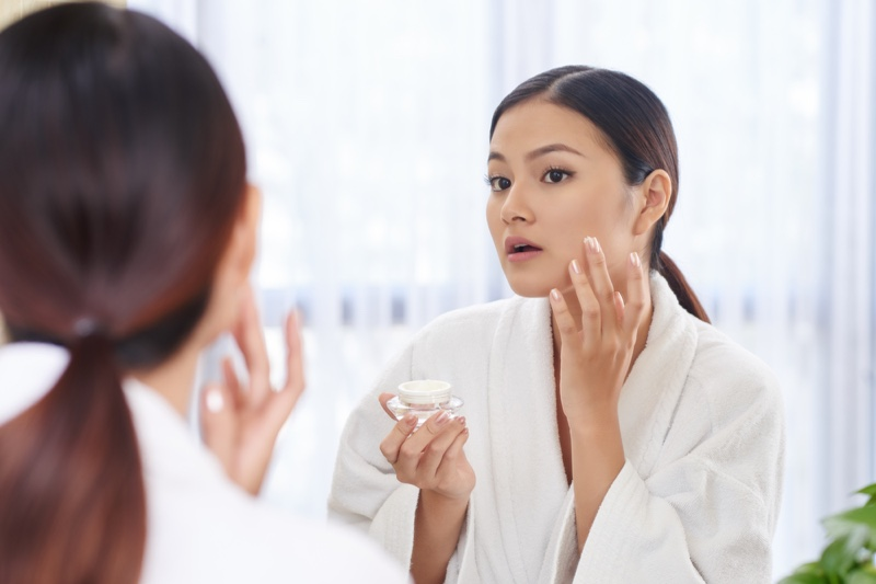 Asian Woman Applying Cream Skin Mirror