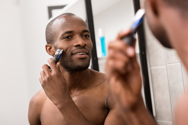 Black Man Using Beard Trimmer Bathroom