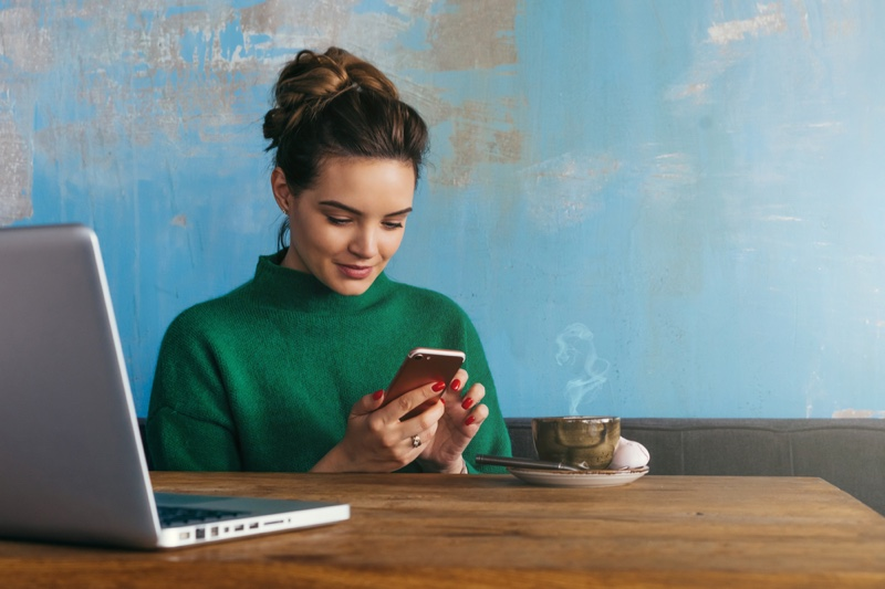Brunette Woman Smiling Holding Phone Laptop Cup Table