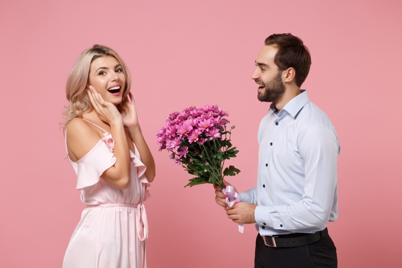 Couple Man Holding Flowers Woman Smiling Pink Dress