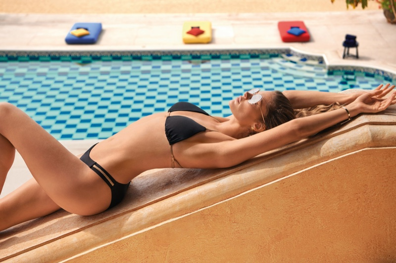 Lounging poolside, Doutzen Kroes poses in Doutzen Stories Hunkemoller swimwear 2020 campaign.