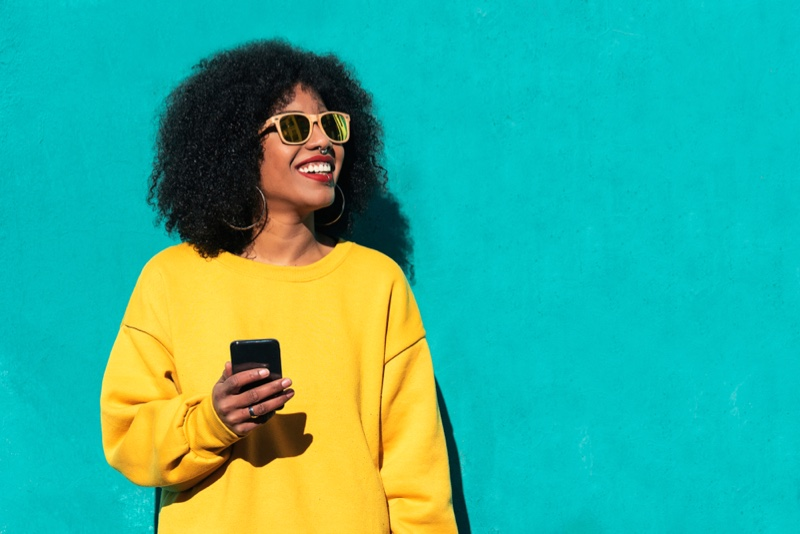 Smiling Black Woman Phone Afro Hair Yellow Sweater Sunglasses