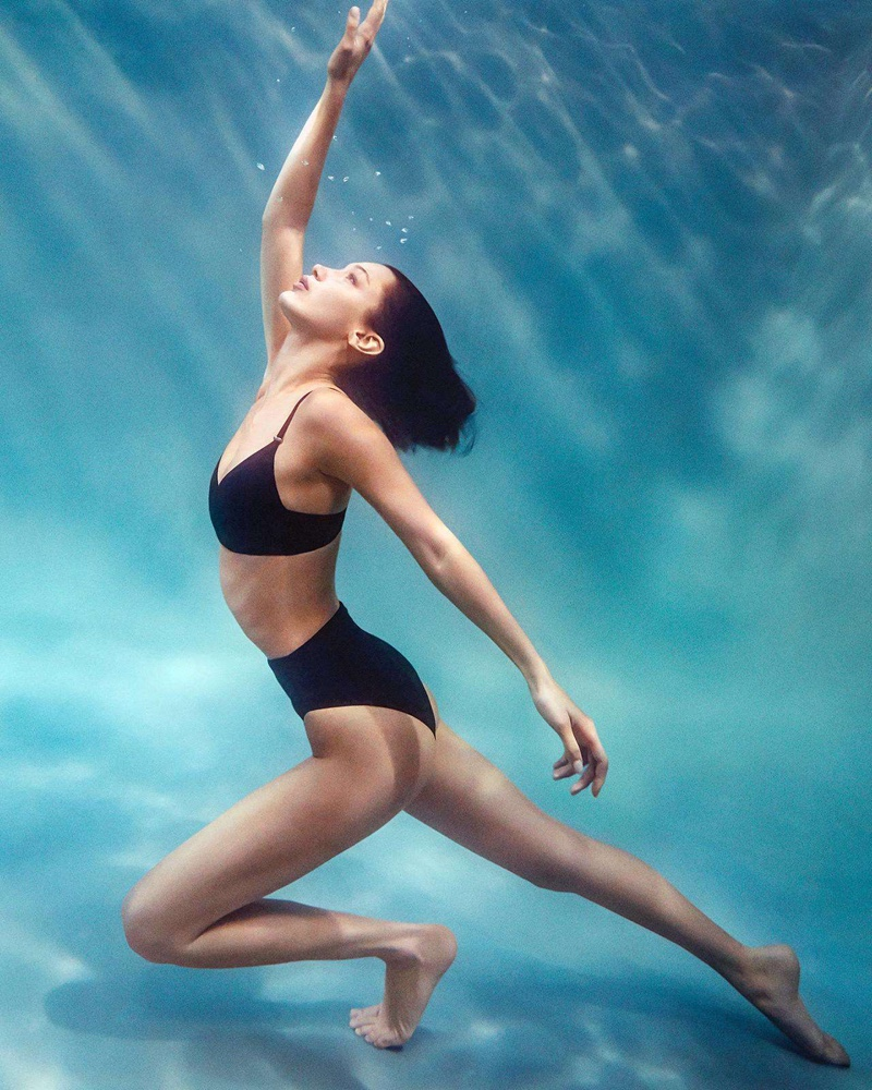 Surrounded by water, Bella Hadid appears in Calvin Klein swimwear summer 2020 campaign.
